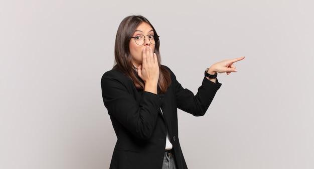 Jonge zakenvrouw die zich gelukkig, geschokt en verrast voelt, de mond bedekt met de hand en naar de laterale kopieerruimte wijst