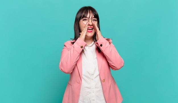 Jonge zakenvrouw die zich gelukkig, opgewonden en positief voelt, een grote schreeuw geeft met de handen naast de mond, roept