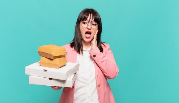 Jonge zakenvrouw die zich gelukkig, opgewonden en verrast voelt, opzij kijkend met beide handen op het gezicht