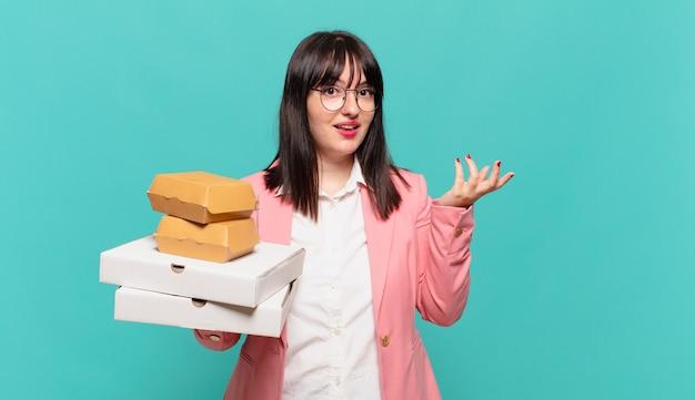Jonge zakenvrouw die zich gelukkig, verrast en opgewekt voelt, lacht met een positieve houding, een oplossing of idee realiseert