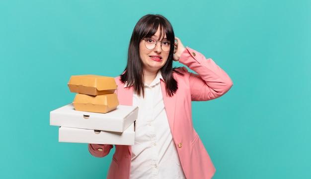 Jonge zakenvrouw die zich gestrest, bezorgd, angstig of bang voelt, met de handen op het hoofd, in paniek bij vergissing