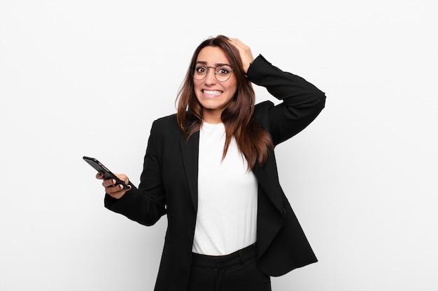 Jonge zakenvrouw die zich gestrest, bezorgd, angstig of bang voelt, met de handen op het hoofd, in paniek raakt bij een fout en een mobiele telefoon vasthoudt