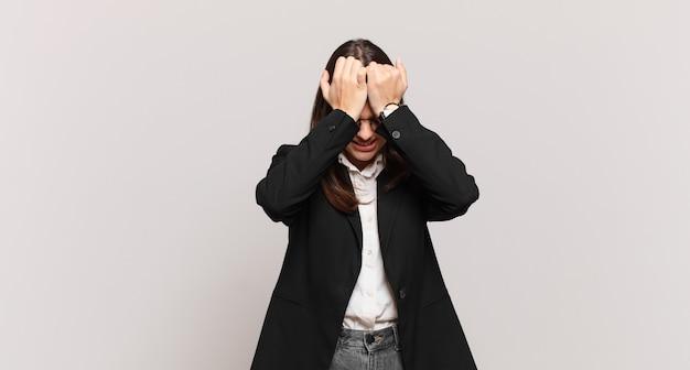 Jonge zakenvrouw die zich gestrest en angstig, depressief en gefrustreerd voelt met hoofdpijn, beide handen opstekend