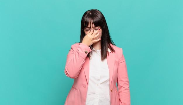 Jonge zakenvrouw die zich gestrest, ongelukkig en gefrustreerd voelt, het voorhoofd aanraakt en lijdt aan migraine of ernstige hoofdpijn