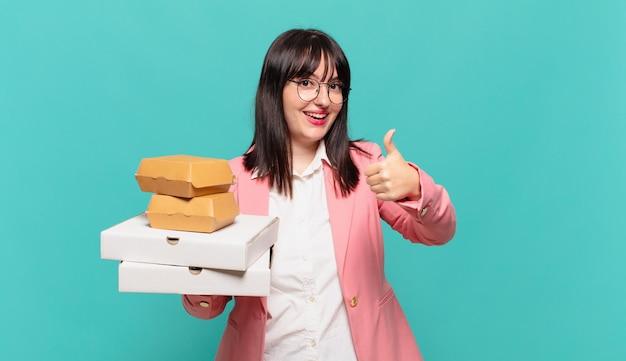 Jonge zakenvrouw die zich trots, zorgeloos, zelfverzekerd en gelukkig voelt, positief glimlachend met duimen omhoog