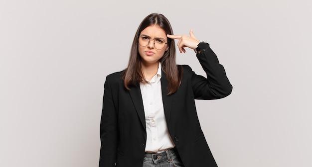 Jonge zakenvrouw die zich verward en verbaasd voelt en laat zien dat je gek, gek of gek bent