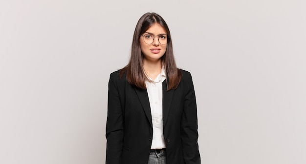 Jonge zakenvrouw die zich verward en verward voelt, met een stomme, verbijsterde uitdrukking die naar iets onverwachts kijkt