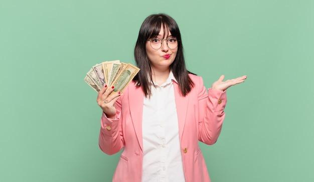 Jonge zakenvrouw die zich verward en verward voelt, twijfelt, weegt of verschillende opties kiest met grappige uitdrukking