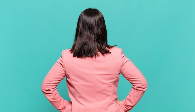 Jonge zakenvrouw die zich verward of vol voelt of twijfels en vragen, zich afvragend, met de handen op de heupen, achteraanzicht