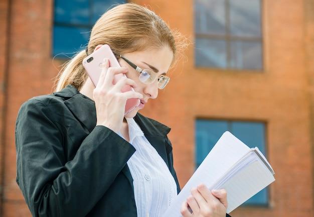 Jonge zakenvrouw documenten in de hand te houden praten op mobiele telefoon
