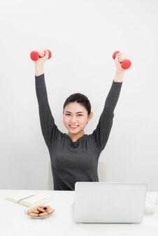Jonge zakenvrouw doet oefening met fitness dumbbells in office