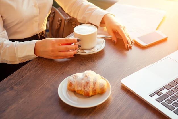 Jonge zakenvrouw drinkt koffie en werkt achter laptop met papieren.