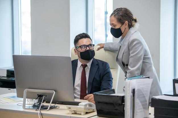 Jonge zakenvrouw en haar collega in maskers computergebruik en interactie