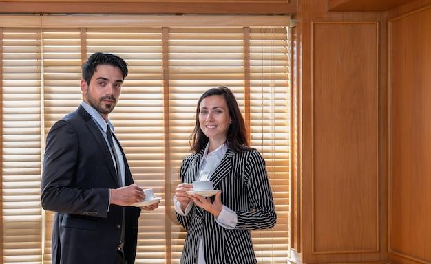 Jonge zakenvrouw en zakenman die pakken draagt en kopjes koffie drinkt terwijl ze naast het blinde raam op kantoor staan. zakelijke bijeenkomsten concept