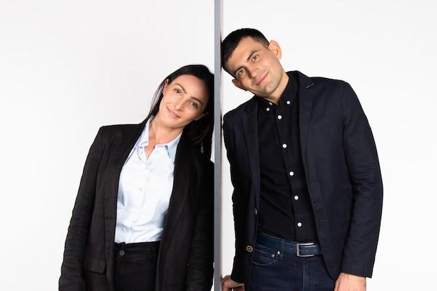 Jonge zakenvrouw en zakenman, gescheiden door een muur, kijken in de camera