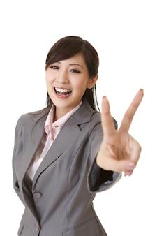 Jonge zakenvrouw geeft je een overwinningsgebaar en glimlacht.