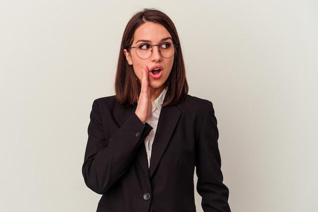 Jonge zakenvrouw geïsoleerd op een witte achtergrond zegt een geheim heet remnieuws en kijkt opzij