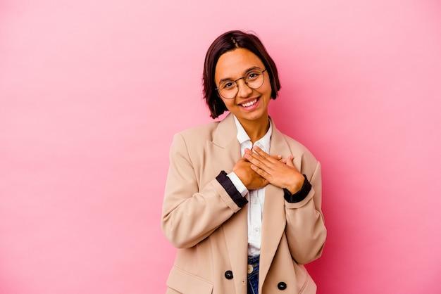 Jonge zakenvrouw geïsoleerd op roze muur heeft vriendelijke uitdrukking, handpalm tegen borst te drukken. liefde concept