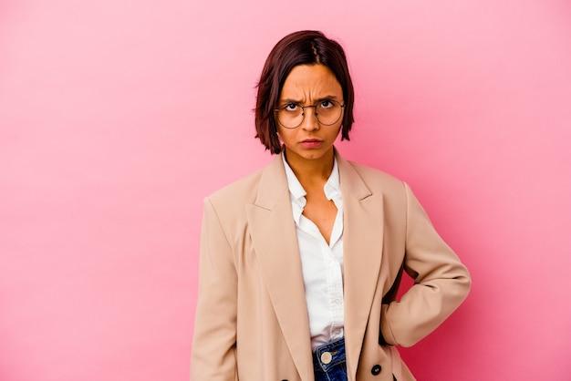 Jonge zakenvrouw geïsoleerd op roze muur verdrietig, ernstig gezicht, zich ellendig en ontevreden voelen