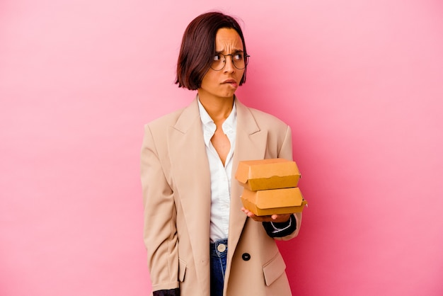 Jonge zakenvrouw geïsoleerd op roze muur verward, twijfelachtig en onzeker