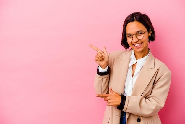 Jonge zakenvrouw geïsoleerd op roze muur wijzend met wijsvingers naar een kopie ruimte, opwinding en verlangen uiten
