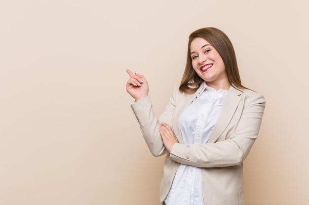 Jonge zakenvrouw glimlachend vrolijk wijzend met wijsvinger weg.