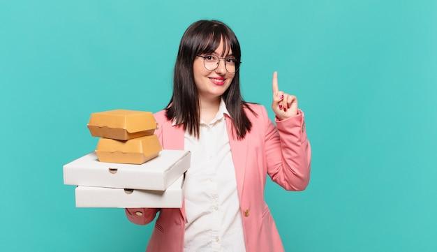 Jonge zakenvrouw glimlacht en ziet er vriendelijk uit, nummer één of eerst met de hand naar voren, aftellend