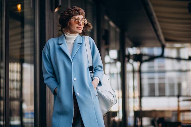 Jonge zakenvrouw in blauwe jas door het café