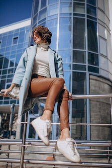 Jonge zakenvrouw in casual outfit door het business center