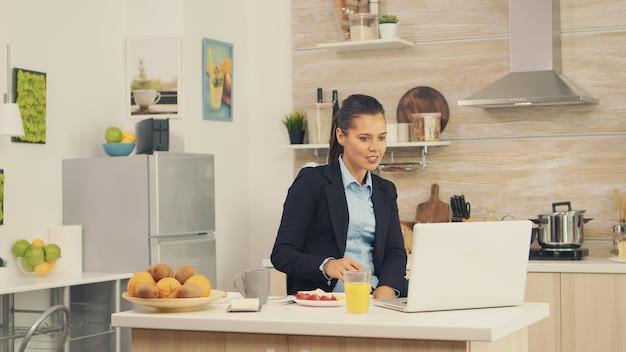 Jonge zakenvrouw in de keuken die een gezonde maaltijd heeft terwijl ze een videogesprek voert met haar collega's van kantoor, moderne technologie gebruikt en de klok rond werkt