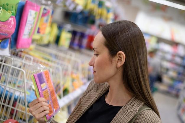 Jonge zakenvrouw in een jas in een supermarkt kiest keuken vodden