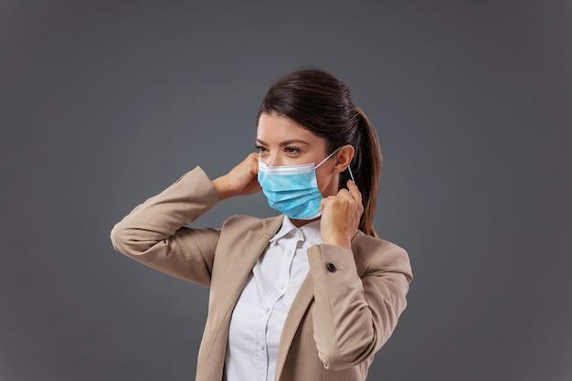 Jonge zakenvrouw in formele kleding die beschermend gezichtsmasker zet tijdens de uitbraak van het coronavirus.