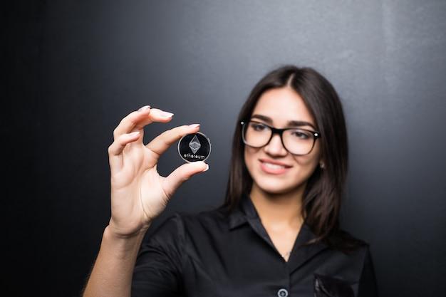 Jonge zakenvrouw in glazen met litecoin in handen geïsoleerd op zwarte muur.