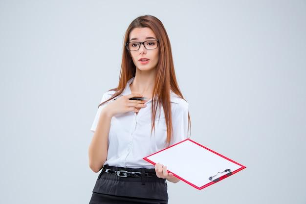 Jonge zakenvrouw in glazen met pen en tablet voor notities over een grijze achtergrond