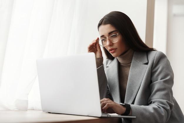 Jonge zakenvrouw in glazen zitten in een kantoorgebouw, werken op een laptop.