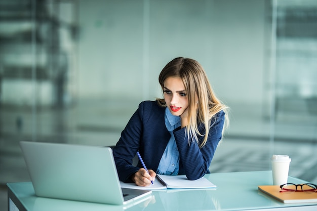 Jonge zakenvrouw in glazen zittend op houten tafel met laptop, plant, wegwerp kopje koffie en schrijven op het papier, met een pen en smartphone