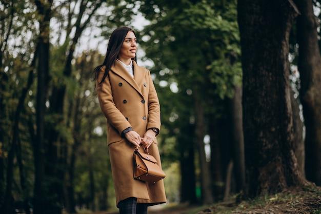Jonge zakenvrouw in jas wandelen in park