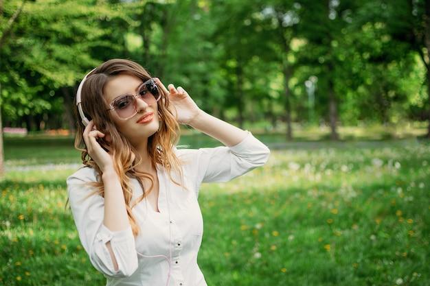 Jonge zakenvrouw in koptelefoon geniet van muziek
