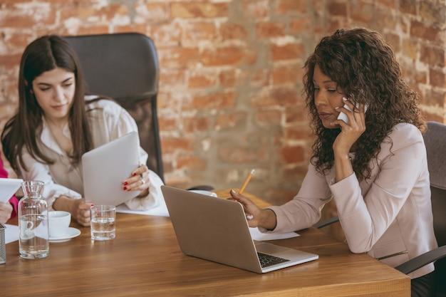 Jonge zakenvrouw in modern kantoor met team creatieve vergadertaken geven