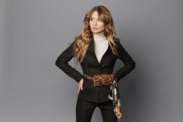 Jonge zakenvrouw in modern pak met luipaard riem tas poseren op een grijze achtergrond, geïsoleerd. mooi modelmeisje in formele kleding en met trendy heuptas met luipaardpatroon. officiële mode