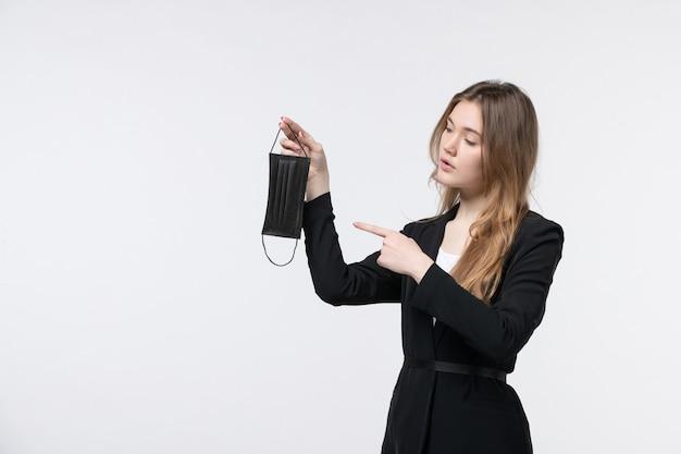 Jonge zakenvrouw in pak die een medisch masker vasthoudt en wijst op een geïsoleerde witte muur