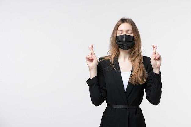 Jonge zakenvrouw in pak met chirurgisch masker en haar vingers kruisend door haar ogen te sluiten op een geïsoleerde witte muur