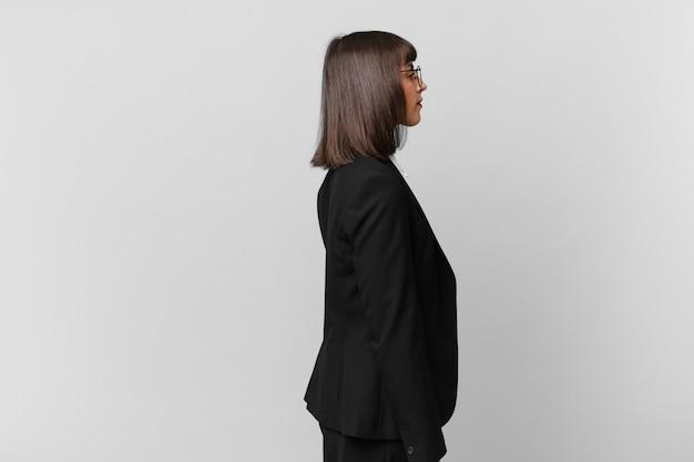 Jonge zakenvrouw in profielweergave die ruimte vooruit wil kopiëren, denken, fantaseren of dagdromen