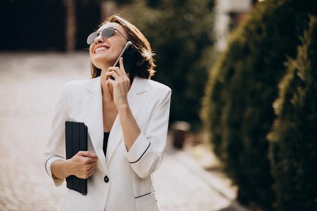 Jonge zakenvrouw in wit pak praten aan de telefoon buitenshuis