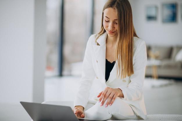 Jonge zakenvrouw in wit pak werken op een computer