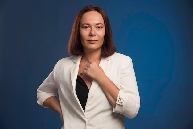 Jonge zakenvrouw in witte blazer in professioneel kapsel.