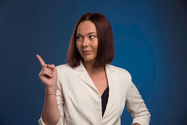 Jonge zakenvrouw in witte blazer met iets.