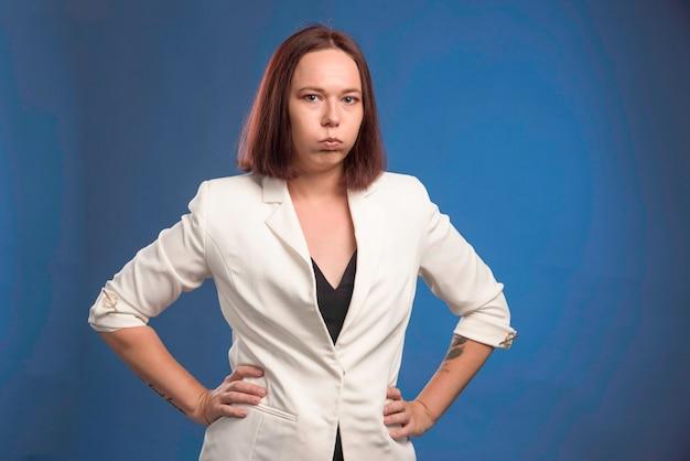 Jonge zakenvrouw in witte blazer ziet er depressief uit.
