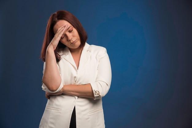 Jonge zakenvrouw in witte blazer ziet er moe uit.