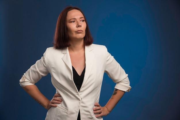 Jonge zakenvrouw in witte blazer ziet er professioneel uit.